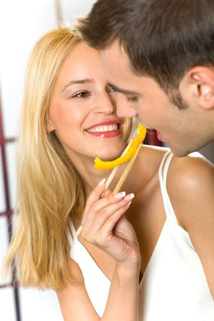 Young attractive couple eating playfully vegetables, indoors photo