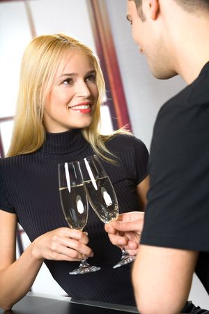 Young attractive couple celebrating with champagne, indoors photo
