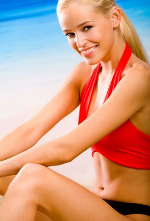 Young sexy woman in sportswear sitting on the beach Stock Photo - 1000828