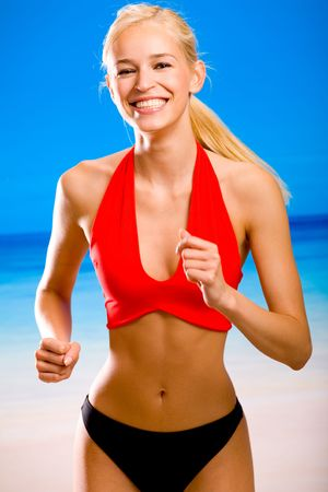 Young attractive woman in sportswear running on beach Stock Photo - 1000829