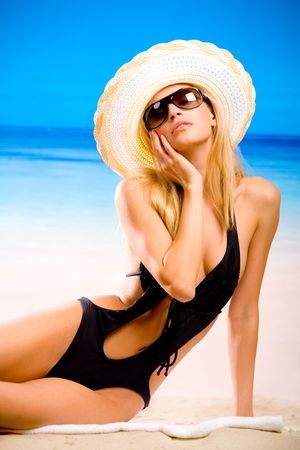 Young beautiful woman in hat and swim wear posing at beach  photo