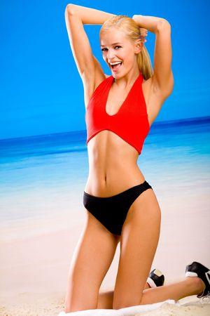sportwear: Young sexy smiling happy woman in sportwear on sea beach