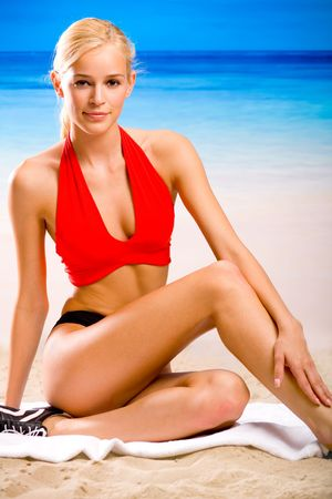 sportwear: Young sexy smiling happy woman in sportwear sitting on the beach Stock Photo