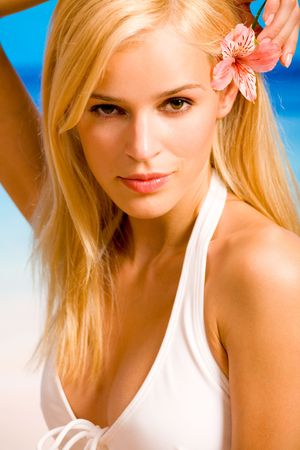 Portrait of young beautiful tanned blond sexy woman in bikini on the beach