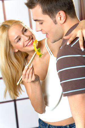 Young attractive happy smiling couple eating playfully vegetables at kitchen photo