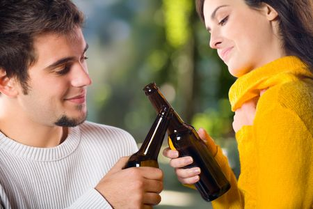 Young attractive happy smiling couple celebrating life event with beer, outdoors photo