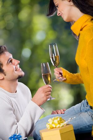 Young happy attractive smiling couple celebrating life event with champagne and gift boxes, outdoors photo