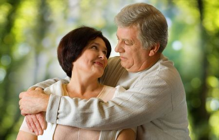 Happy elderly couple embracing outdoors photo