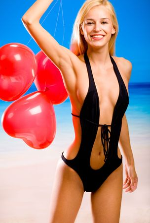 Young beautiful sexy smiling tanned blond woman in bikini on tropical sea beach, holding valentine's balloons Stock Photo - 1165523
