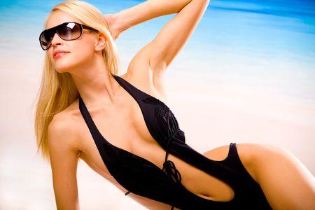 Young beautiful sexy tanned happy woman in sunglasses and bikini laying during sunbath on sea beach Stock Photo - 1208903