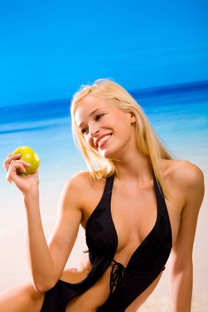 Young sexual beautiful smiling blond woman with apple in bikini on sea beach. You can use top part of image as copy space in your design. Stock Photo - 1281634
