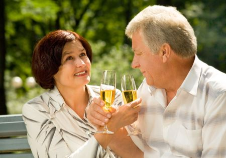 Happy successful attractive elderly couple celebrating anniversary, life event or holiday together with champagne, outdoors photo