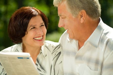 Happy smiling attractive elderly couple reading together outdoors Stock Photo - 1320136