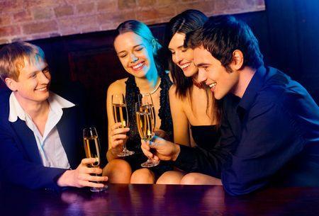 Two young happy smiling couples with champagne glasses at celebration, party or  date in night club photo