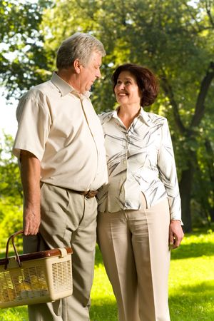 Senior attractive happy smiling couple walking in park, looking at each other, man carrying picnic basket Stock Photo - 1328148