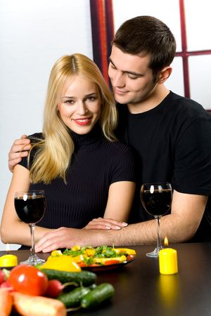 Young attractive happy smiling couple celebrating with red wine at kitchen photo