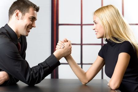 domination: Young happy couple or business people fighting in arm-wrestling Stock Photo