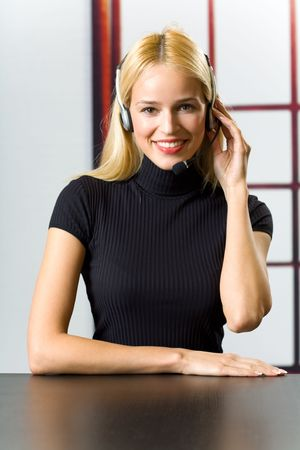 hot secretary: Young attractive smiling businesswoman or secretary with headset at office Stock Photo