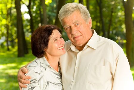 couple enlac�: Couples heureux attrayants a�n�s embrassant en parc