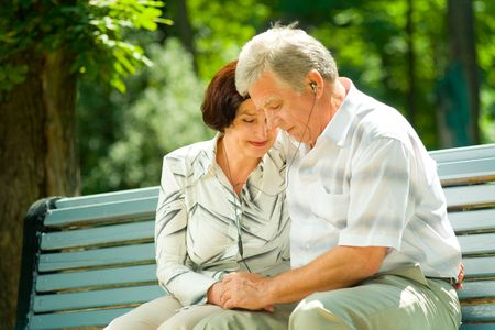 praying together: Happy elderly couple listening music in headset or praying together, outdoors Stock Photo