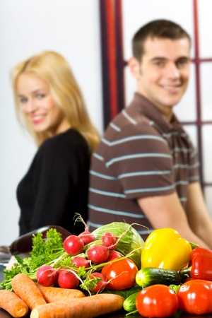 Vegetables on the table and blurred young happy smiling couple on background photo