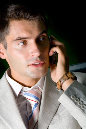 mobilephones: Young happy successful businessman on cellphone, dark tone