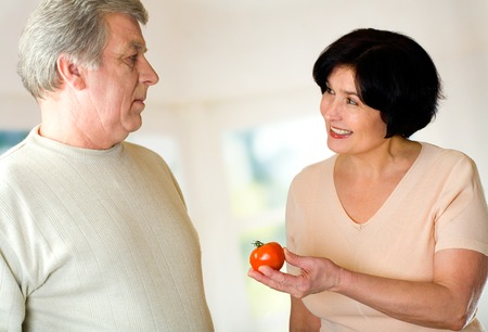 Happy mature couple with tomato at kitchen photo
