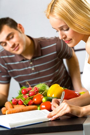 studing: Young happy attractive woman studing and man cooking at kitchen. Focus on woman. Stock Photo