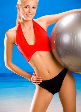 Young attractive woman in sportswear doing with pilates gym ball on sea beach photo