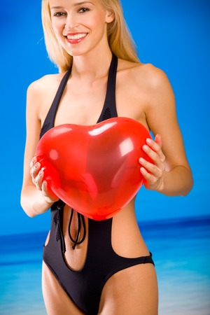 Young beautiful sexy smiling tanned blond woman in bikini on tropical sea beach, holding valentines balloon photo