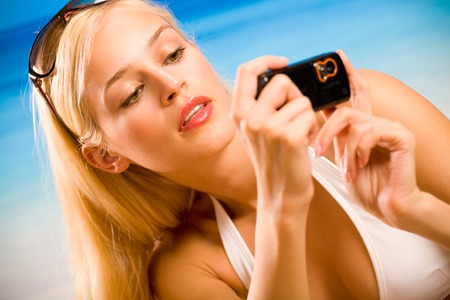 Young beautiful tanned happy smiling blond woman in bikini taking photograph by cellphone on sea beach photo