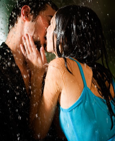 erotic couple: Young happy amorous couple kissing and hugging under a rain Stock Photo
