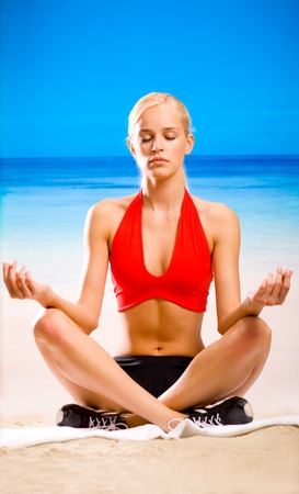 Young woman doing yoga moves or meditating on tropical ocean beach photo