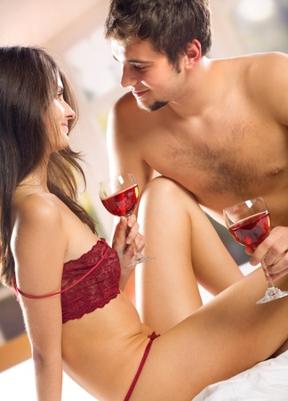 Young happy couple celebrating with red wine at bedroom Stock Photo - 1677003