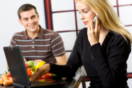 Young happy smiling attractive businesswoman with cellphone and laptop, cooking man at kitchen. Focus on woman. photo