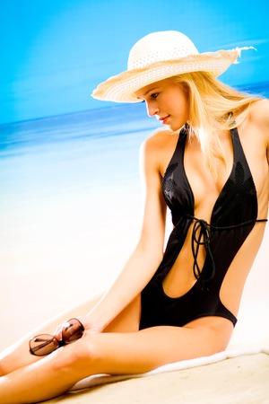 sunbath: Gelooide mooie jonge blonde vrouw in de hoed en bikini tijdens zonnebaden op zee strand