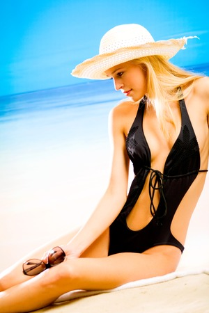 Young beautiful tanned blond woman in hat and bikini during sunbath on sea beach photo