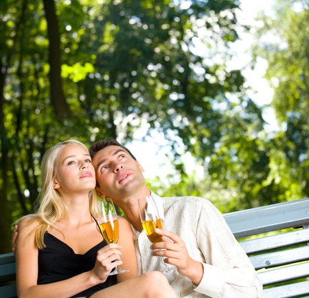 Young couple celebrating with champagne outdoors. To provide maximum quality I have made this image by combination of two photos. photo