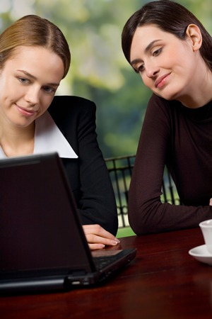 Two young business female on laptop, outdoors photo