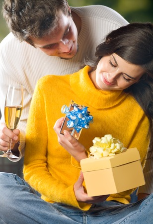 Young happy couple with gifts and champagne outdoors photo