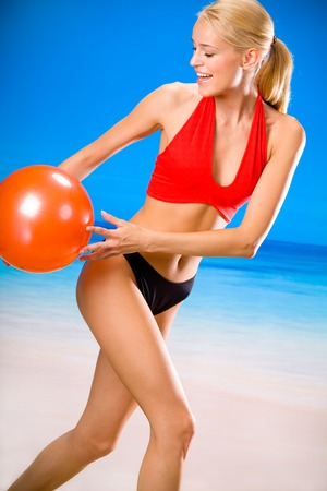 Young beautiful happy woman playing with gym ball on beach Stock Photo - 1737457