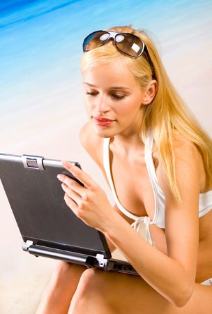 Young beautiful woman in bikini with laptop on sea beach photo