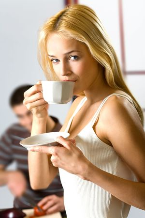 Young drinking woman with cup and cooking man at kitchen. Focus on woman. photo