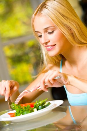 Portrait of young happy smiling woman eating salad Stock Photo - 1834179