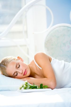 Portrait of young beautiful sleeping woman with gifts on bed at bedroom photo