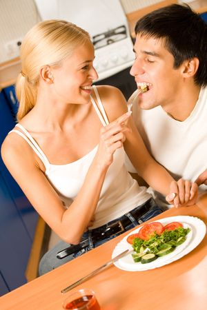 Funny scene of young happy couple playfully eating at kitchen photo
