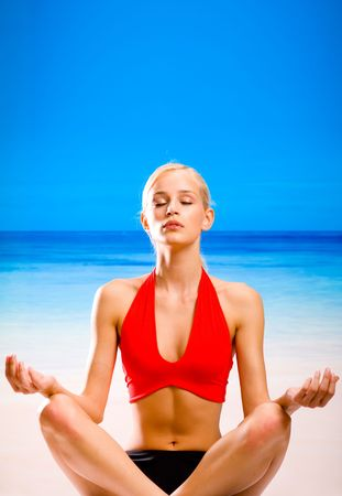 Young woman doing yoga moves or meditating on sea beach. You can use top part as copyspace. photo