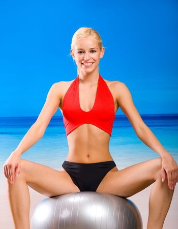Young woman in sportswear with pilates gym ball on sea beach photo