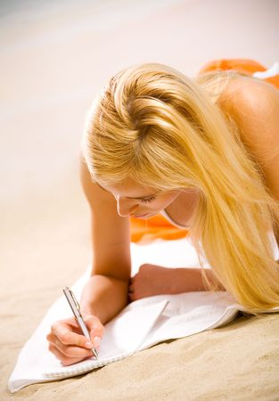 Young beautiful woman in bikini writing on sea beach photo