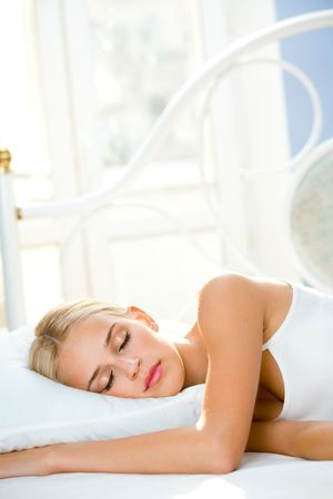 Portrait of young beautiful sleeping woman on bed at bedroom photo